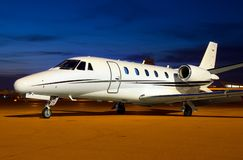 Private luxury jet is waiting for next night departure. The white private luxury jet is waiting for next night departure with dark blue sky behind Stock Images