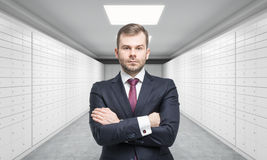 A private manger of a bank with crossed hands is standing in a room with safe deposit boxes. A concept of storing of important doc Stock Photo