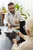 Private medical practice. Grandma pays the doctor for a visit to a private doctor`s office. The patient is giving money to the doctor for a medical appointment Stock Images