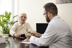 Private medical practice. Grandma pays the doctor for a visit to a private doctor`s office. The patient is giving money to the doctor for a medical appointment Royalty Free Stock Image