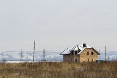 Private modern two-storey house under construction without a fence in a field in winter.  Royalty Free Stock Photo