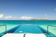 Private None edge swimming pool in the ocean. A none edge swimming pool located on the coral reef in the ocean. The island is away from the swimming pool, you Royalty Free Stock Photo