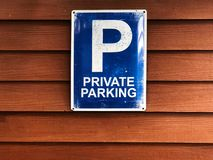 Private parking sign on wooden wall. Blue sign and white color text `Private parking`. Copy space royalty free stock photo