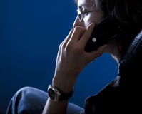 Private phone call. Young man on a private phone call royalty free stock photos