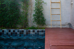 Private pool in the garden. Private pool with blue mosaic tile and red planks in the garden Stock Photography