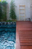 Private pool in the garden with red planks. Private pool with blue mosaic tiles with red planks in the garden Stock Photography