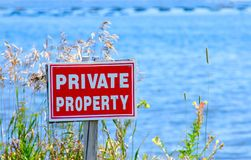 Private Property. White on red private property sign by the ocean Stock Photography
