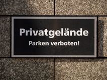 Private Property and no parking sign at wall in German language. Private Property and no parking sign at grey granite wall at day with white letters on black in Stock Photos