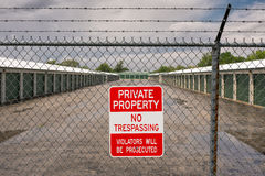 Private property no trespassing. Private property and no trespassing sign on barbed wire fence in front of self storage facility Royalty Free Stock Photos