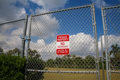 Private Property No Trespassing Sign on Fence. A red and white metal sign saying Private Property No Trespassing Violators Will Be Prosecuted hangs on a chain Stock Photography