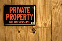 Private property no tresspassing. A private property sign on a tall privacy fence Stock Photography
