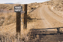Private property sign and cattle guard along road