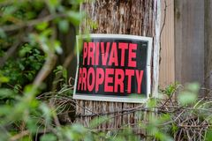 Private property sign on post. Closeup of a private property sign stapled to barbed wire post with thorns Royalty Free Stock Photo