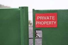 Private property sign red on green closed shut gate at Loch Lomond rural estate Scotland. Uk royalty free stock image