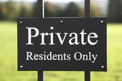 Private residents only sign. Closeup of private residents only warning sign on gate with green grass in background Stock Photography