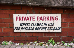 Private road Parking Warning. Sign on a private road - Private parking, Wheel clamps In use Fee Payable before release Stock Images