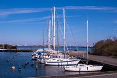 Private sailing yachts are moored up in Copenhagen under blue sk royalty free stock photography