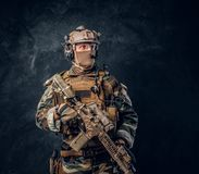 Elite unit, special forces soldier in camouflage uniform posing with assault rifle. Private security service contractor in camouflage uniform posing with stock photos