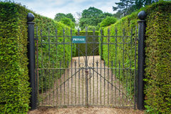 Private sign attached to an ornate wrought iron gate Royalty Free Stock Images