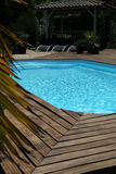 Private swimming pool with long chairs and gazebo Royalty Free Stock Images