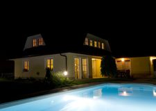 Private swimming pool at night. A beautifully lit swimming pool and a house at night Royalty Free Stock Photos