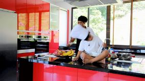 Private Thai chef cooking, his little son in chef`s hat nearby sitting on the table in a modern style home kitchen. Kid is eating, stock video footage
