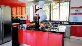 Private Thai chef cooking, his little son in chef`s hat nearby sitting on the table in a modern style home kitchen. Kid is eating, stock footage