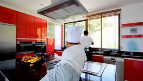 Private Thai chef cooking, his little son in chef`s hat nearby sitting on the table in a modern style home kitchen. Kid is eating, stock video
