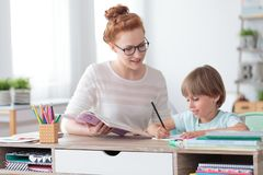 Private tutor helping young student. Female private tutor helping young student with homework at desk in bright child`s room stock images