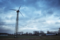 Private wind turbine. A single wind turbine for private use against cloudy sky stock images
