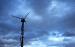Private Wind Turbine. A low angle view of a small private wind turbine shot against a dark cloudy sky royalty free stock photos