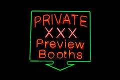 Private XXX neon sign. Red, pink and green neon sign of the words 'Private XXX Preview Booths' on a black background Royalty Free Stock Photo