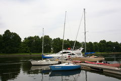 Private yachts, motorboats and boats moored at the old wooden pier. Stock Image