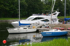 Private yachts, motorboats and boats moored at the old wooden pier. Royalty Free Stock Photography