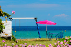 Private yard by a seaside. Yard by a seaside with metal table under beach umbrella and children swing Royalty Free Stock Images