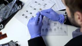 Privater Detektiv, der Fingerabdrücke auf Kugel unter Verwendung der Pinzette, Untersuchung überprüft stockbilder