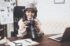 Privates Detektivbüro Kleines Mädchen sitzt am Schreibtisch, der in camera Fotos betrachtet stockfoto