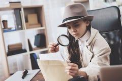 Privates Detektivbüro Kleines Mädchen sitzt am Schreibtisch, der Fotos mit Lupe betrachtet stockbild