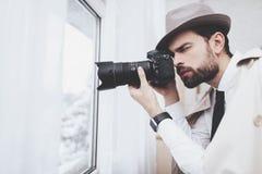 Privates Detektivbüro Mann macht Fotos im Fenster stockfotografie