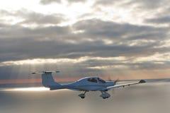 Privates flaches Flugwesen über Meer am Sonnenuntergang Stockfotografie