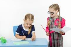 Privlezhnaya pupil under the supervision of a strict teacher Royalty Free Stock Photo
