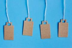 Prix à payer bruns vides de carton, étiquette de vente, étiquette de cadeau, étiquette -adresse sur le fond bleu images libres de droits