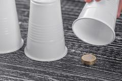 Prix au-dessous d'une de trois tasses en plastique dans une escroquerie sur une table en bois noire images stock