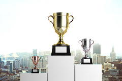 Prize concept. Golden, silver and bronze winner`s cups placed on white pedestals. City background. Prize concept. Mock up, 3D Rendering royalty free illustration