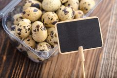 Prize tag with quail eggs. Organic quail eggs with prize tag. Natural gourmet meal stock photos