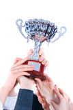 Prize-winning cup in hands of a command Royalty Free Stock Photos