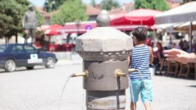 PRIZREN - IL KOSOVO, LUGLIO 2015: Acqua potabile della gente dal rubinetto orientale al quadrato del centro urbano archivi video
