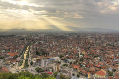 Prizren at sunset. City scape of second biggest city Prizren in Kosovo at sunset with red roofed houses and mosques and river. In the background a mountain range Stock Photo