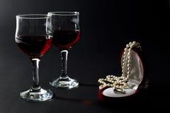 Pärlemorfärg halsband och guld- cirkel i smyckenask med två vinglas som fylls med rött vin som isoleras på svart Fotografering för Bildbyråer