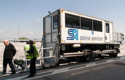 PRM passenger mobility assistance vehicle at airport runway. Passengers are getting off of an airport passenger mobility assistance vehicle, also known as PRM Royalty Free Stock Images